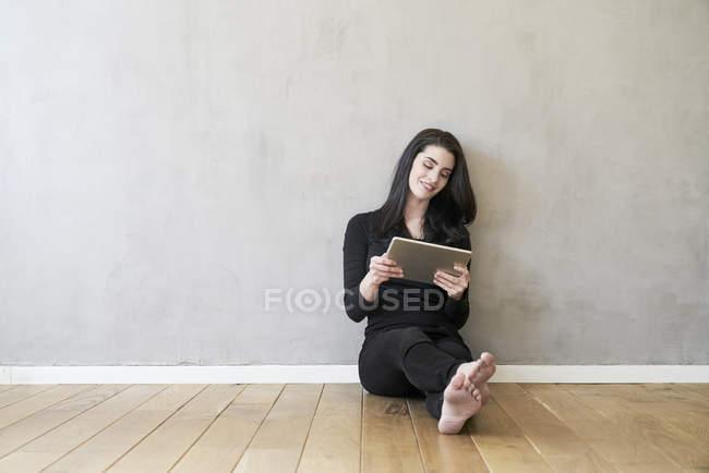 Женщина сидит на полу и с помощью планшета — стоковое фото