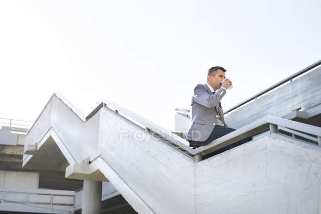 Businessman sitting on stairs with takeaway coffee — Stock Photo