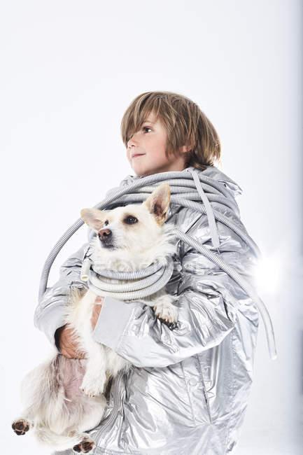Мальчик в маскарадной одежде с собакой — стоковое фото