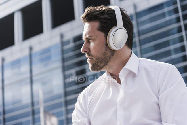 Homem de negócios usando fones de ouvido — Fotografia de Stock