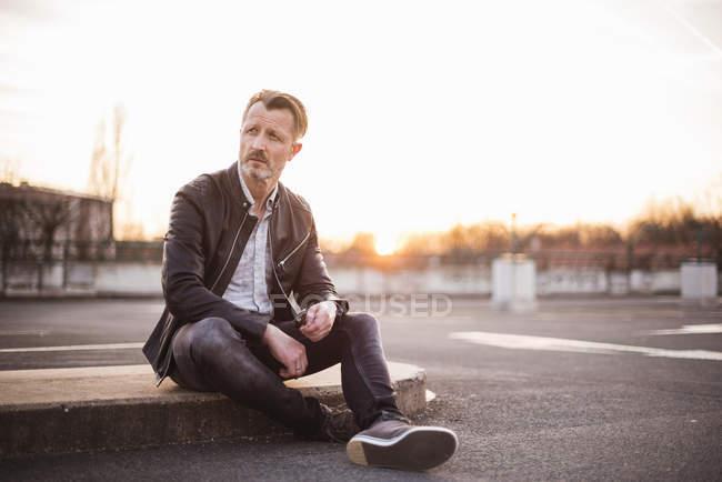 Homem sentado no parque de estacionamento — Fotografia de Stock