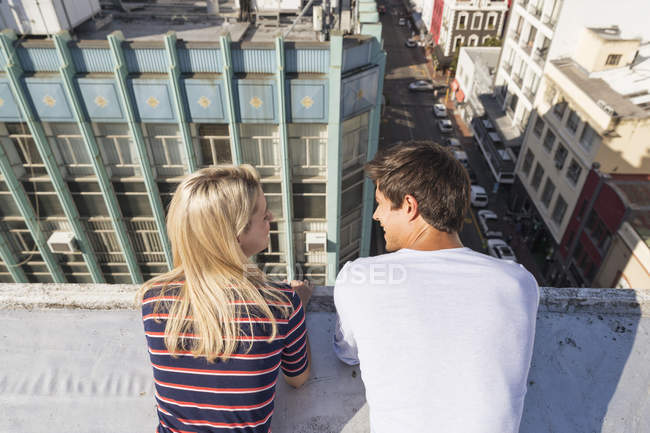 Couple talking on rooftop terrace — Stock Photo