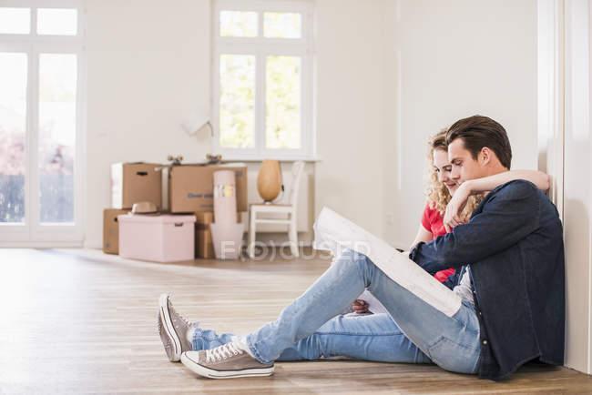 Junges Paar in neuem Zuhause sitzt auf dem Boden und betrachtet Grundriss — Stockfoto