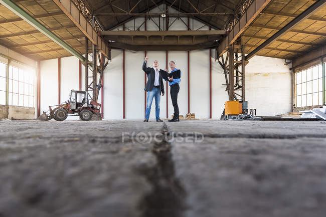 Businessmen talking in old industrial hall — Stock Photo