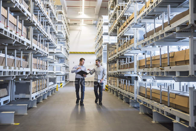 men interacting in factory warehouse stock photo 164883184