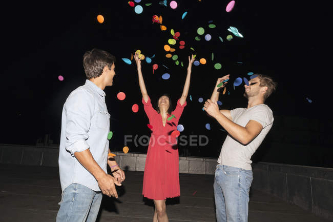 People throwing confetti on rooftop party — Stock Photo