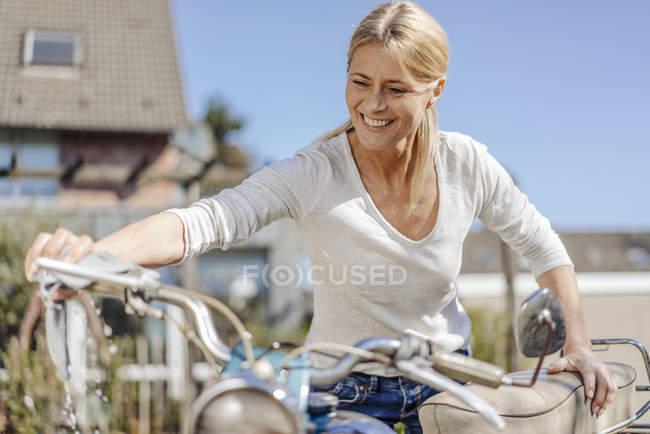 Mujer limpieza vintage motocicleta - foto de stock