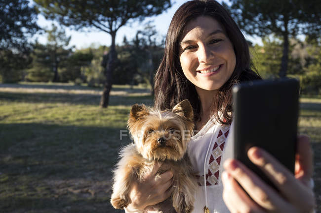 Woman taking selfie with dog — Stock Photo