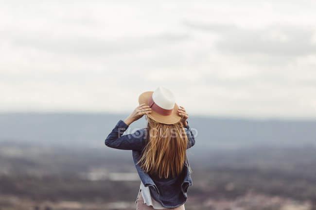 Frau mit Hut schaut in die Ferne — Stockfoto