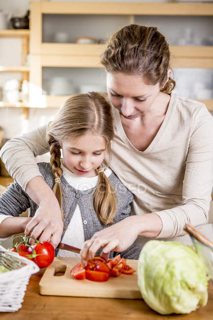 Mother and daughter cutting tomatoes — Stock Photo