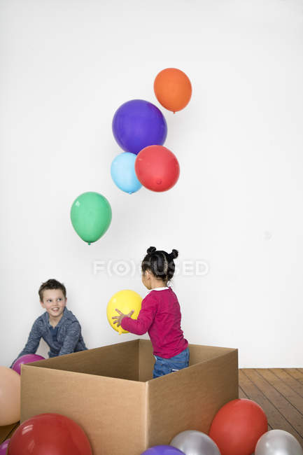 Two kids playing with balloons — Stock Photo