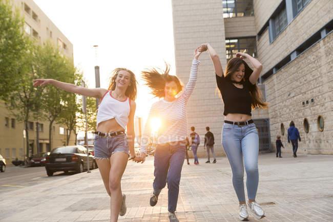 Mulheres jovens correndo de mãos dadas — Fotografia de Stock
