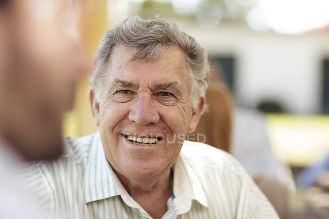 Homme senior souriant socialisation sur une Garden-Party — Photo de stock