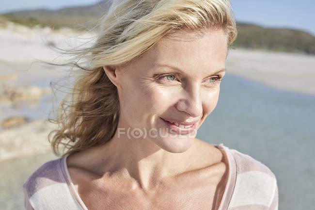 Женщина наслаждается солнцем на берегу моря — стоковое фото