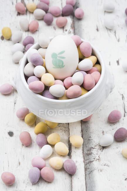 Ovos de Páscoa de chocolate e ovos de Páscoa pintados em tigela — Fotografia de Stock