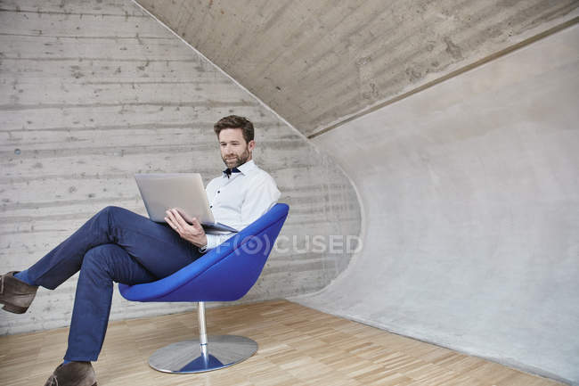 Businessman sitting on chair and using laptop — Stock Photo