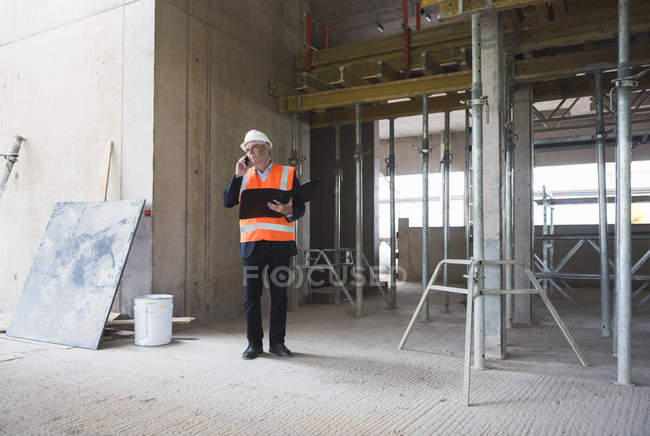 Man on phone in building under construction — Stock Photo