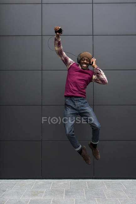 Man jumping while listening music — Stock Photo