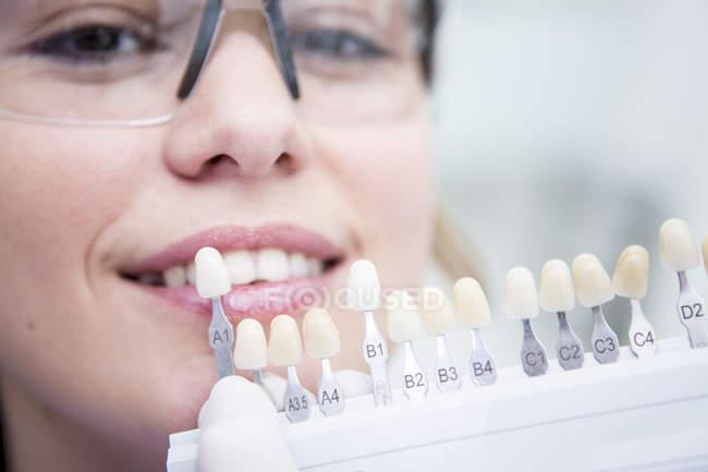 Donna a dentista che sceglie il colore per denti — Foto stock