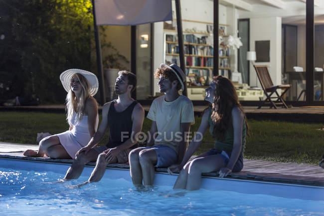 Amis, assis au bord de la piscine — Photo de stock