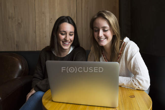 Amigos sonrientes usando laptop - foto de stock