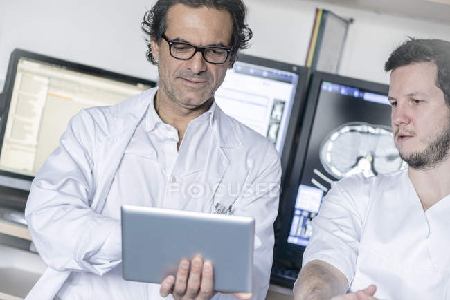 Two doctors holding and looking at tablet — Stock Photo