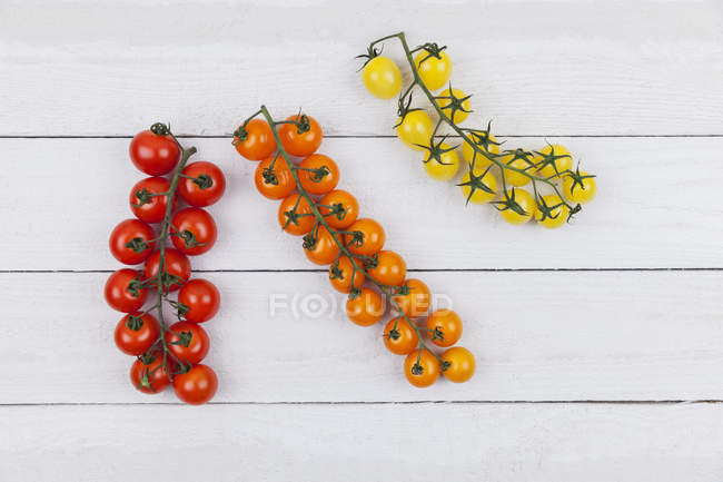 Various bunch tomatoes on wooden background — Stock Photo