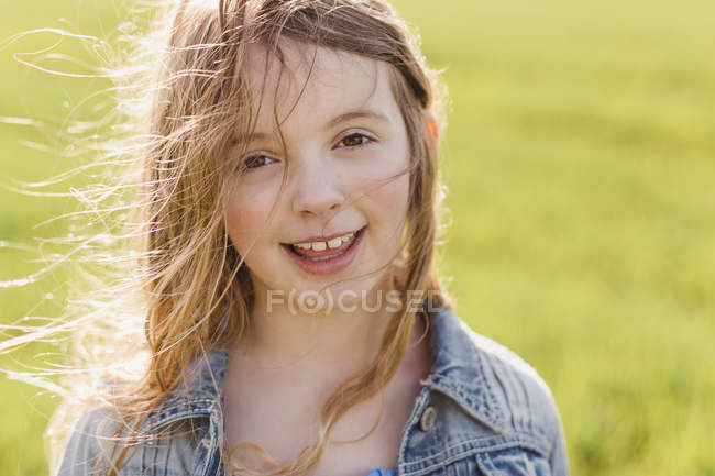Girl with blowing hair looking at camera — Stock Photo