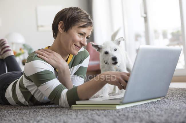Frau liegt mit Hund auf dem Boden — Stockfoto