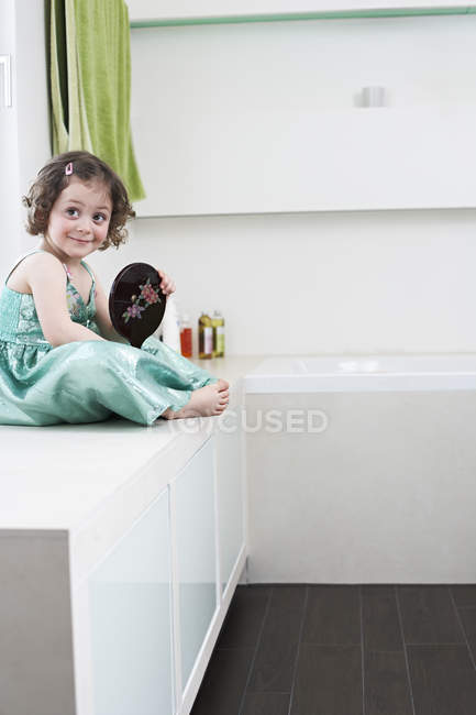 Smiling little girl with hand mirror — Stock Photo