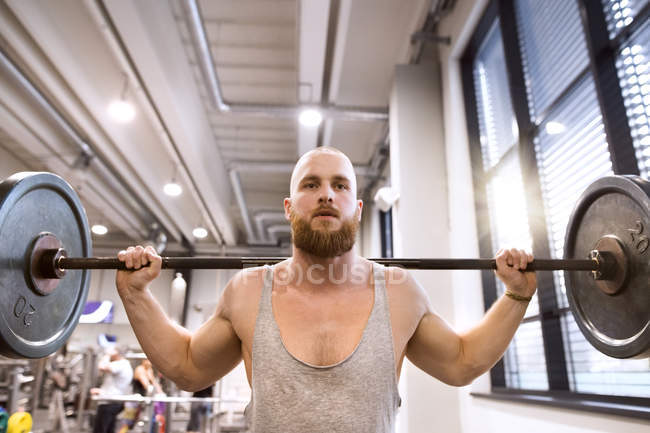 Man lifting weights in gym — Stock Photo