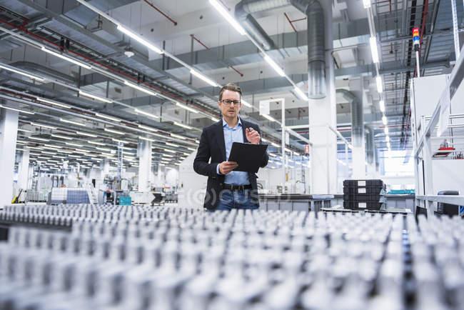 Человек проверяет продукцию на заводе — стоковое фото