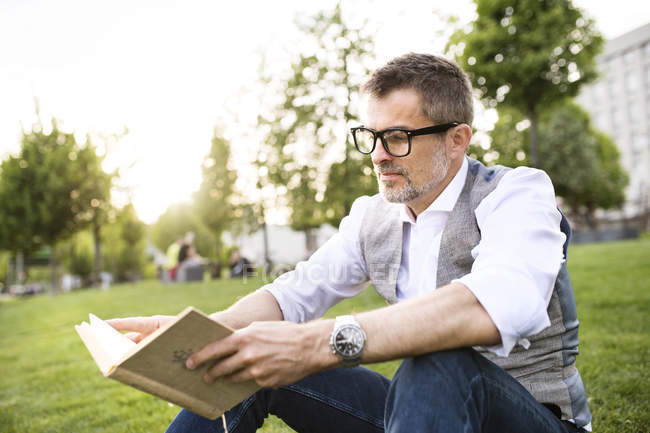 Businessman sitting on grass and reading book — Stock Photo