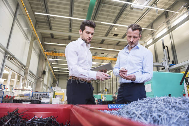 Businessmen standing near containers with shreds — Stock Photo