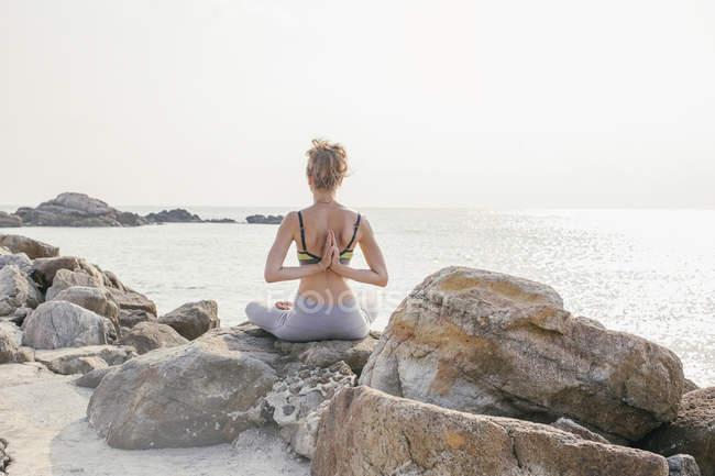 Mujer sentada en asiento de loto, meditando en la playa — Stock Photo