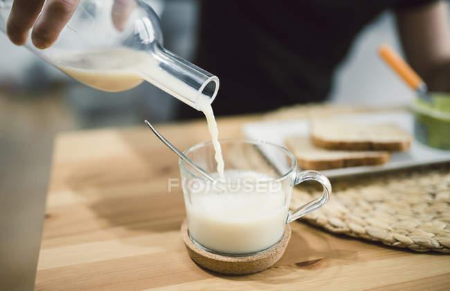 Pouring milk into glass — Stock Photo