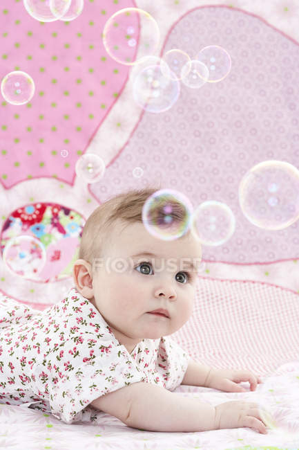 Baby girl watching soap bubbles — Stock Photo