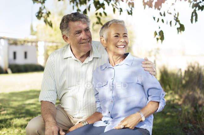 Glückliches Seniorenpaar sitzt auf der Bank im Garten — Stockfoto