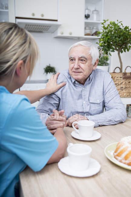 Nurse listening to elderly patient — Stock Photo