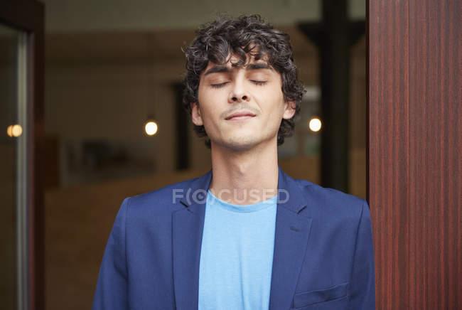 Чоловік, що стоїть в офісі з закритими очима — стокове фото
