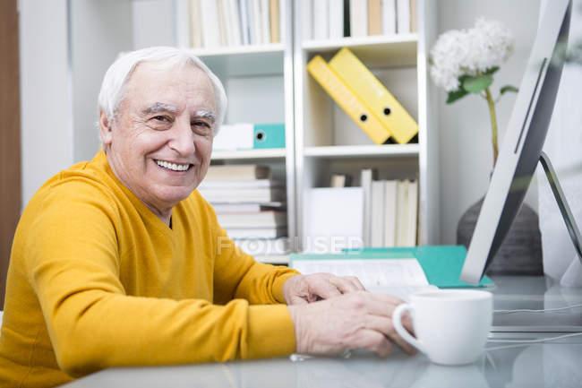Senior man working at computer — Stock Photo