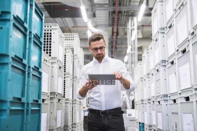 Человек, использующий планшет в цехе — стоковое фото