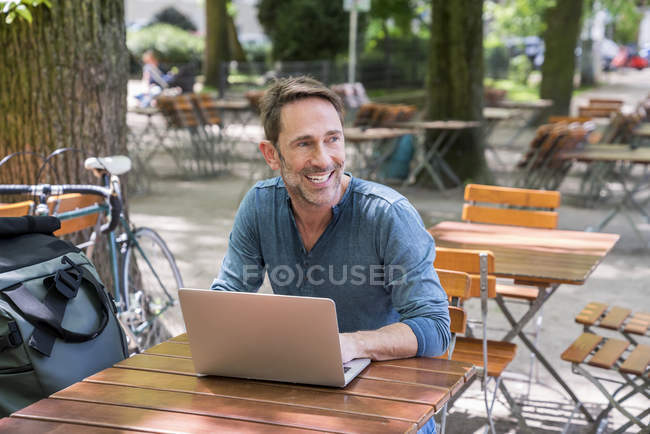 Человек с ноутбуком в пивном саду — стоковое фото