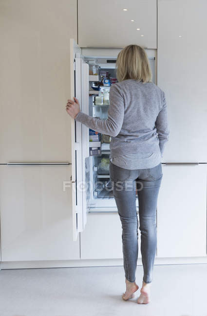 Woman looking into fridge — Stock Photo