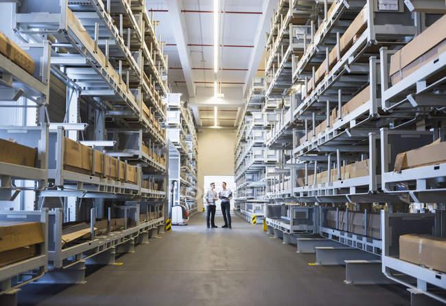 Hommes interagissant dans l'entrepôt de l'usine — Photo de stock