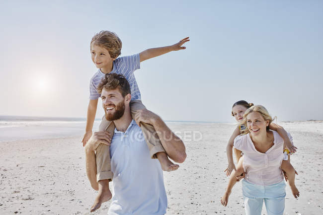 Family strolling on beach — Stock Photo