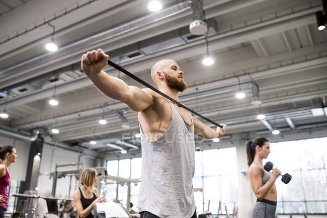 Man exercising with fitness band — Stock Photo