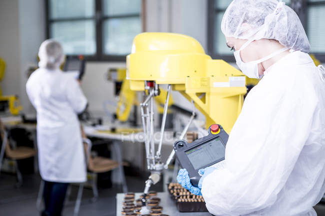 Женщина на заводе изучает печенье робота — стоковое фото