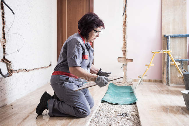 Woman laying tiles at construction site — Stock Photo