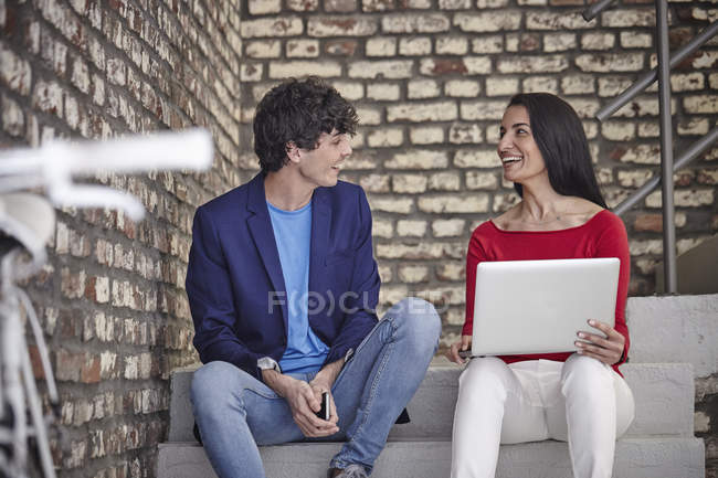 Colegas sentados nas escadas e usando laptop — Fotografia de Stock